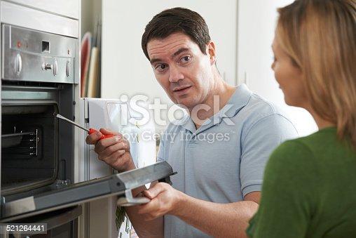 istock Engineer Giving Woman Advice On Kitchen Repair 521264441