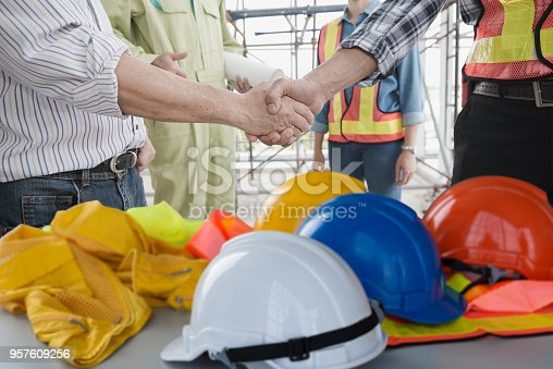 Engineer group asia handshake of congratulations with helmet on a desk. The success and safety in the workplace.