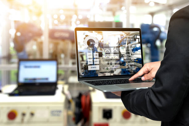 Hand mit Laptop mit Maschine-Real-Time monitoring Systemsoftware-Ingenieur. Unschärfe Automatisierung Roboter Arm Maschine smart Factory Industrie 4. Iot, digitale Herstellung Technologie Bedienkonzept. – Foto