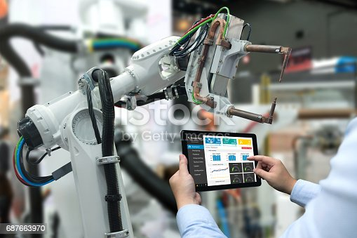 istock Engineer hand using tablet, heavy automation robot arm machine in smart factory industrial with tablet real time monitoring system application. Industry 4th iot concept. 687663970