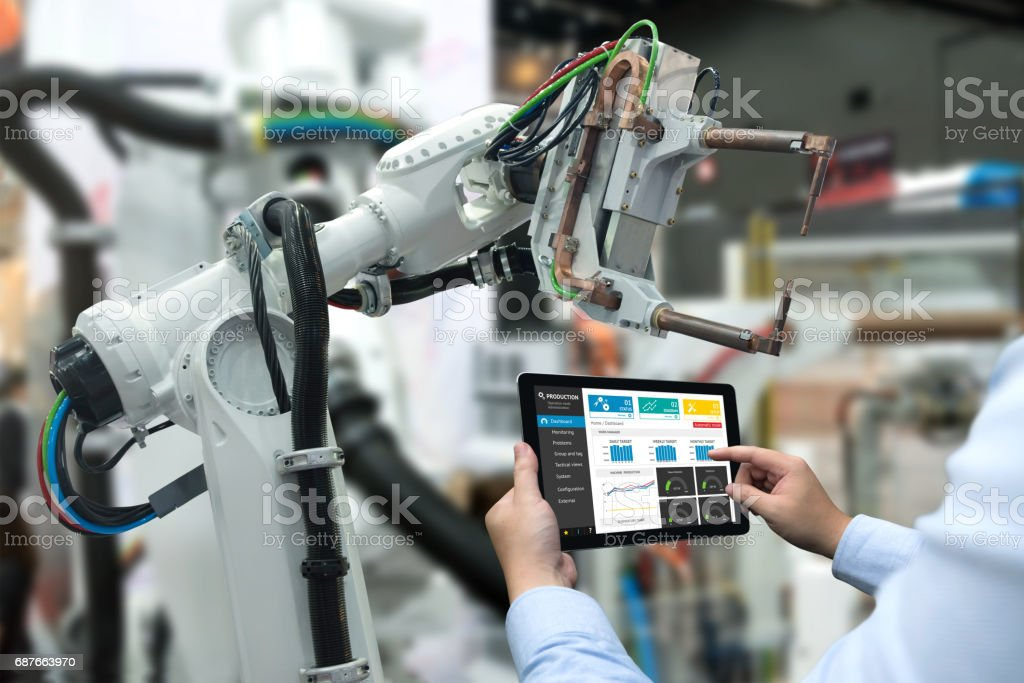 Engineer hand using tablet, heavy automation robot arm machine in smart factory industrial with tablet real time monitoring system application. Industry 4th iot concept. стоковое фото