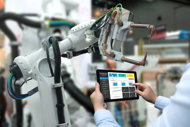 Main à l'aide de la tablette, machine à bras robot lourd automation dans smart usine industrielle avec tablette application du système de surveillance en temps réel de l'ingénieur. L'industrie 4e ITO concept. - Photo