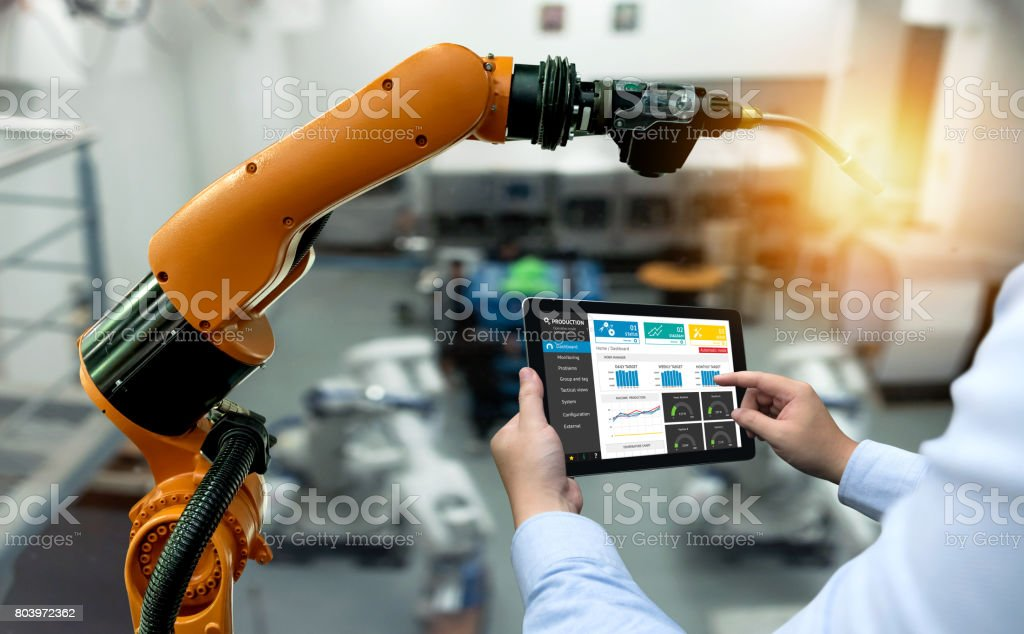 Engineer hand using tablet, heavy automation robot arm machine in smart factory industrial with tablet real time monitoring system application. Industry 4th iot concept. stock photo