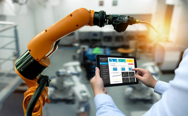 Engineer hand using tablet, heavy automation robot arm machine in smart factory industrial with tablet real time monitoring system application. Industry 4th iot concept. – zdjęcie