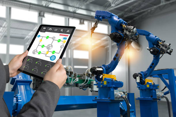 Engineer hand using tablet, heavy automation robot arm machine in smart factory industrial with tablet real time process control monitoring system application. Industry 4th iot concept. stock photo
