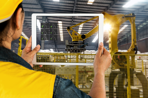 istock Engineer hand using tablet, heavy automation robot arm machine in smart factory industrial with tablet real time monitoring system application. Industry 4th iot concept. 914921068