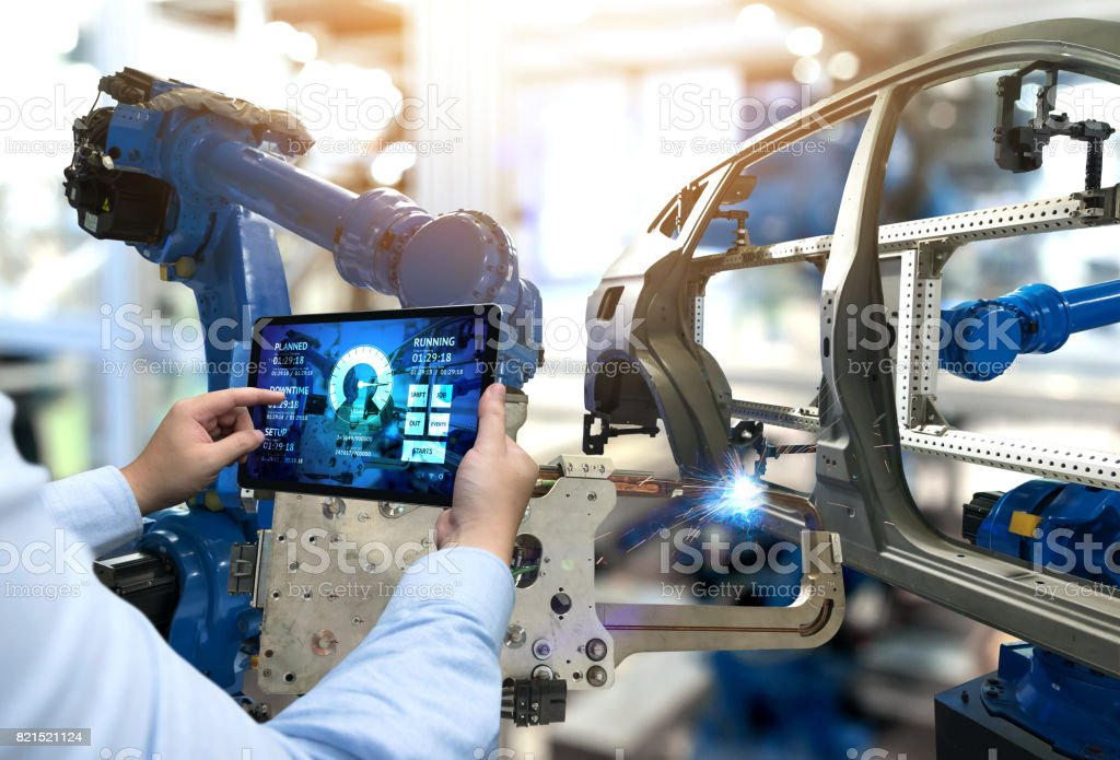 Engineer hand using tablet with machine real time monitoring system software. Automation robot arm machine in smart factory automotive industrial Industry 4th iot , digital manufacturing operation. royalty-free stock photo