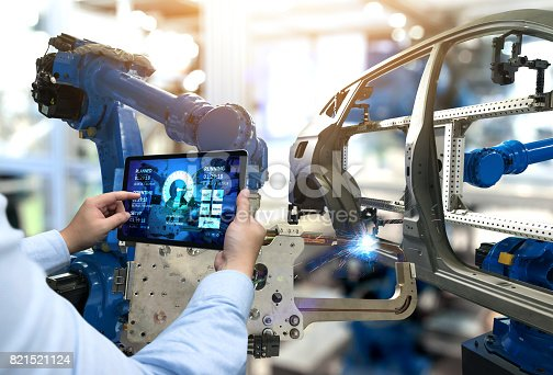 istock Engineer hand using tablet with machine real time monitoring system software. Automation robot arm machine in smart factory automotive industrial Industry 4th iot , digital manufacturing operation. 821521124