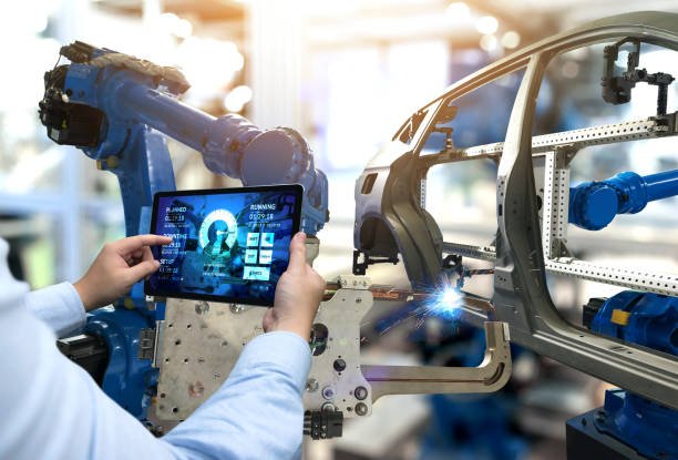 Engineer hand using tablet with machine real time monitoring system software. Automation robot arm machine in smart factory automotive industrial Industry 4th iot , digital manufacturing operation. stock photo