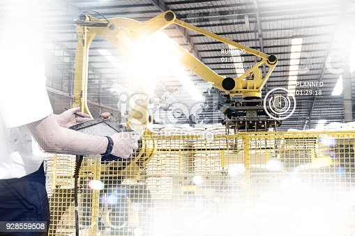 istock Engineer hand using tablet with machine real time monitoring system software. Automation robot arm machine in smart factory automotive industrial Industry 4th iot , digital manufacturing operation. 928559508