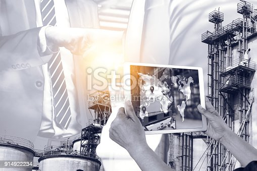istock Engineer hand using tablet with supply chain logistic monitoring system software and smart factory industry 4th iot , digital manufacture. Double exposure of bump hand business successful. 914922234