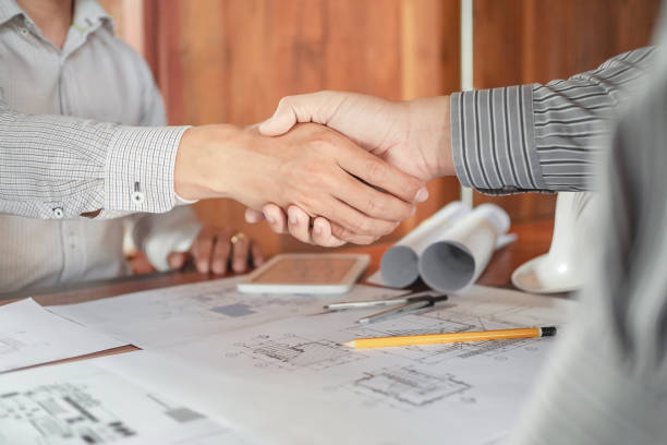 Engineer handshake together with blueprint in workplace. stock photo