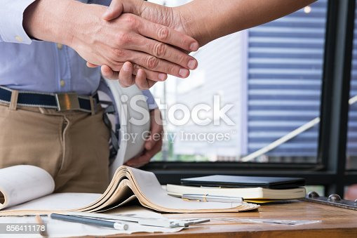 istock engineer handshaking for successful deal in construction plan. architect shake hand for agreement in new business project at workplace. 856411178