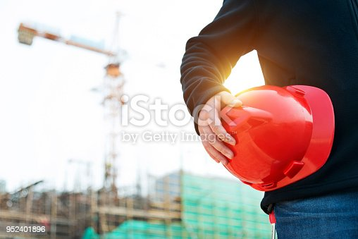 Engineer holding a hardhat under his arm.