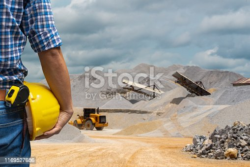 508140747 istock photo Engineer holding a yellow helmet for the safety of workers on a background of coal mining trucks are driving on the road. 1169527686