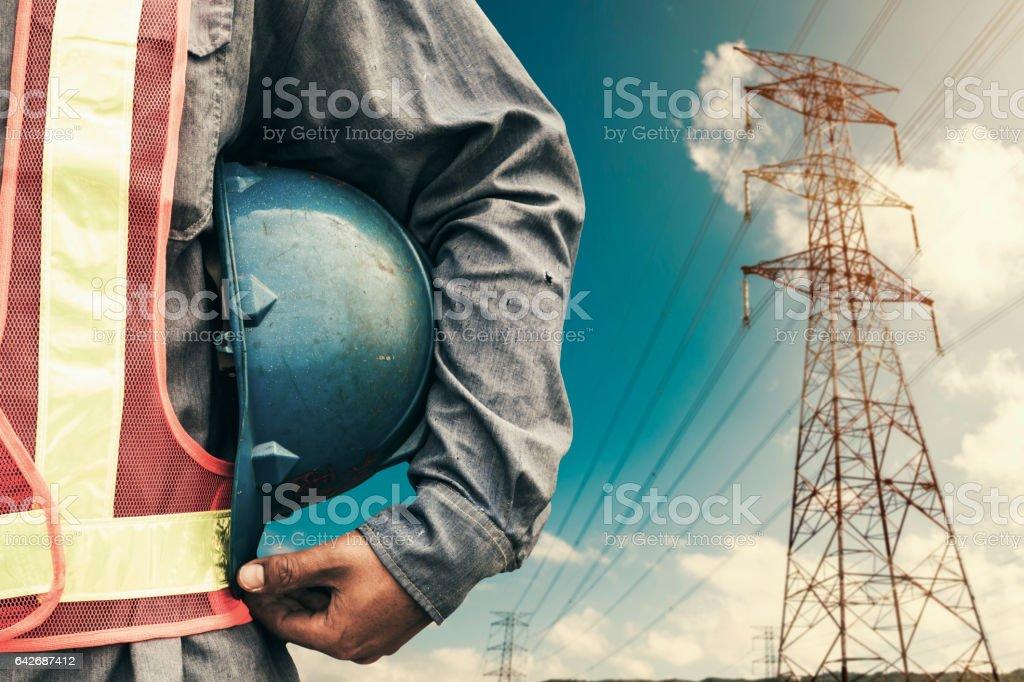 Ingenjör som innehar blå hjälm stående på högspännings-tornet bildbanksfoto