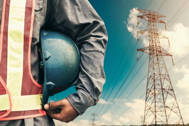 高圧鉄塔の立っている青いヘルメットを保持しているエンジニア - 電気部品 ストックフォトと画像