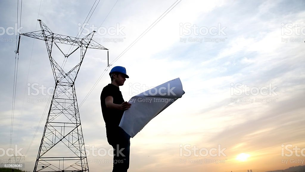engineer holding blueprints under the power lines. stock photo