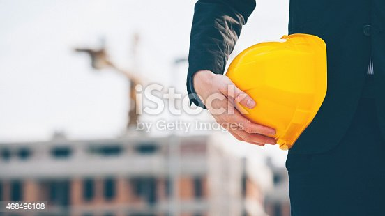 istock Engineer holding hard hat at construction site close up shot 468496108
