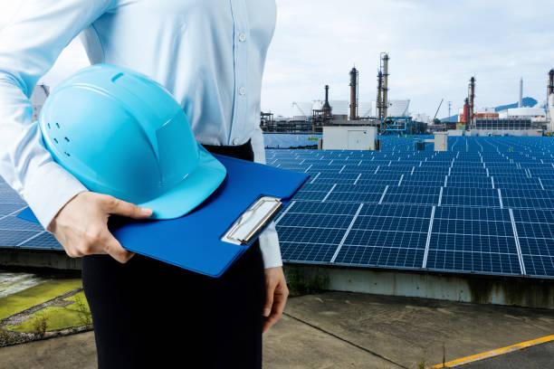 engineer holding helmet and solar power plant. renewable energy concept. stock photo