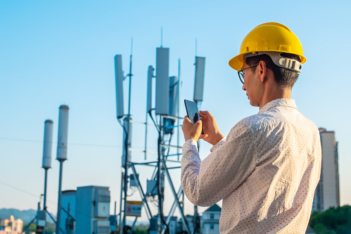 Engineer holding mobile phone testing the communications tower