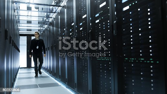 802317162istockphoto IT Engineer Holding Notebook and Walking Through Data Center Full of Working Rack Servers. 802320806
