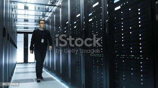 802317162istockphoto IT Engineer Holding Notebook and Walking Through Data Center Full of Working Rack Servers. 802320826