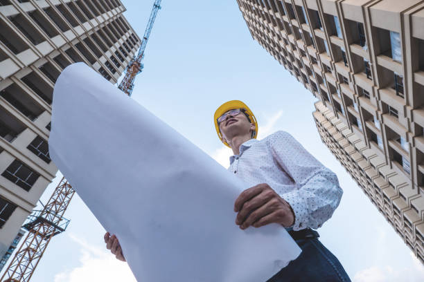 Engineer holding plans at a construction site stock photo