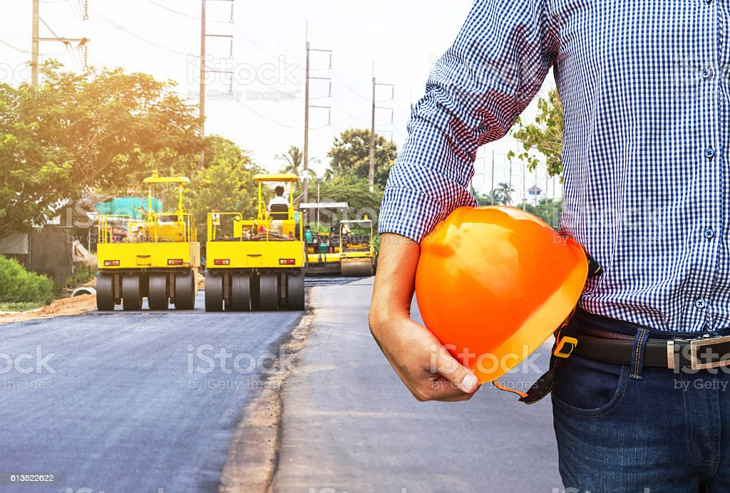 engineer holding safety helmet at road construction site stock photo