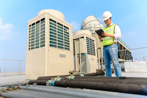Engineer holding tablet  is checking the cooling tower on the roof of the building to be in good condition.