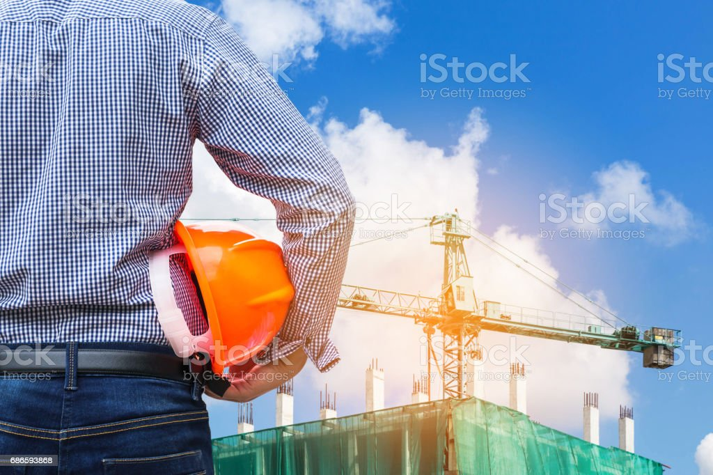 engineer holding yellow safety helmet in building construction site royalty-free stock photo
