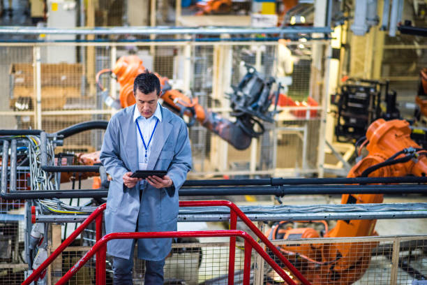 engineer in a factory using a digital tablet - robotics manufacturing stock photos and pictures