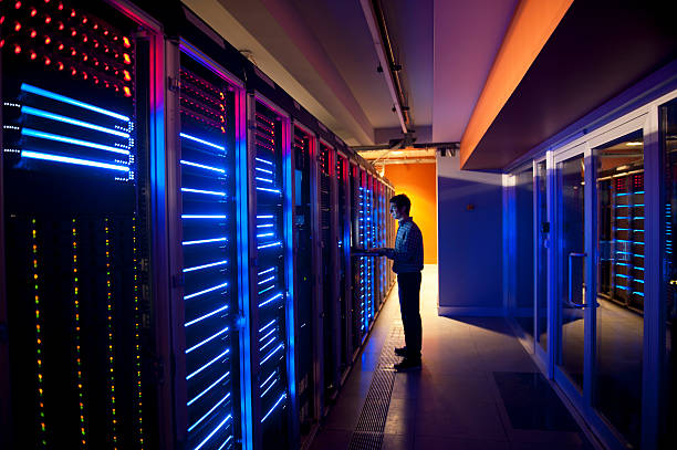 IT Engineer in Action Configuring Servers Modern interior of server room in datacenter. IT Engineer in Action Configuring Servers telecommunications equipment stock pictures, royalty-free photos & images