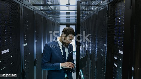 802303672 istock photo IT Engineer in Data Center Opens Server Rack Cabinet Door and Connects to It with His Laptop. Runs Diagnostics. 802301240