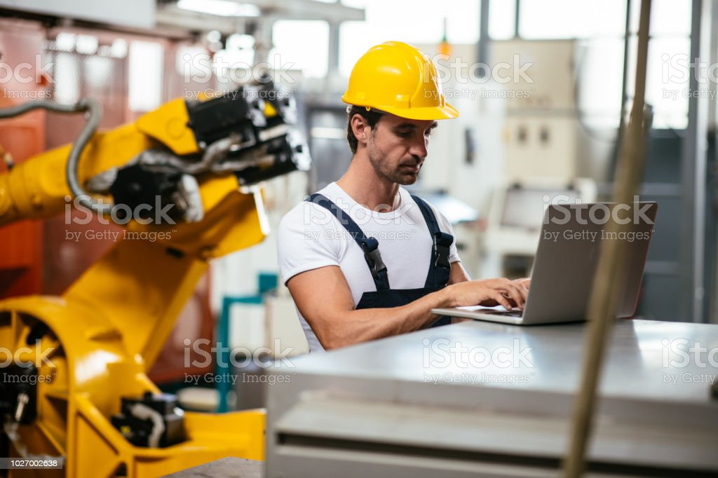 Engineer in factory controlling production. Shallow DOF. Developed...