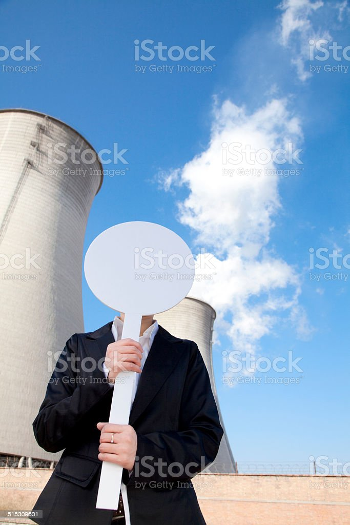 Engineer in front of cooling towers with sign stock photo