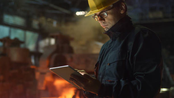 engineer in glasses using tablet pc in foundry. industrial environment. - metallurgy stock photos and pictures