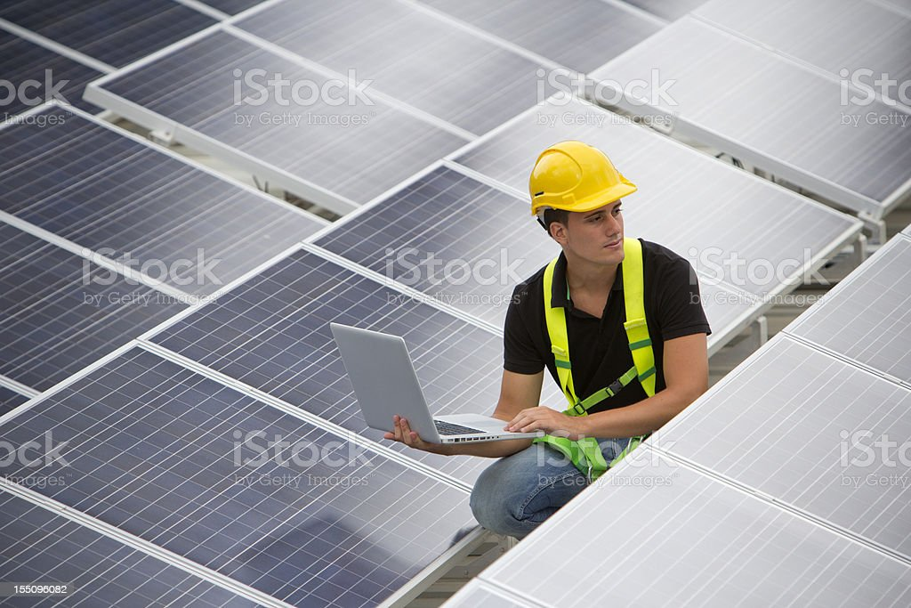Engineer in hard hat working on solar panel array royalty-free stock photo
