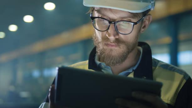 engenheiro em capacete de segurança é usar um computador tablet em uma fábrica de indústria pesada. - equipamento industrial - fotografias e filmes do acervo