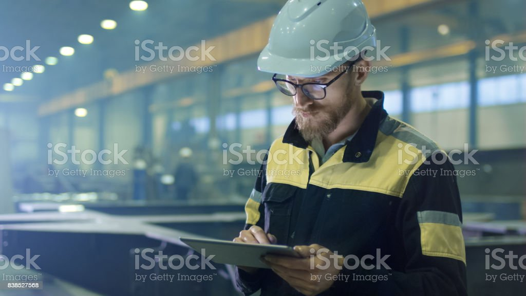 Engineer in hardhat is using a tablet computer in a heavy industry factory. Engineer in hardhat is using a tablet computer in a heavy industry factory. Adult Stock Photo
