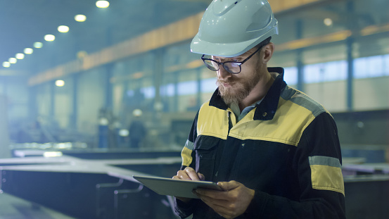 Engineer In Hardhat Is Using A Tablet Computer In A Heavy Industry Factory Stock Photo - Download Image Now