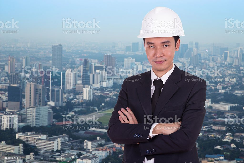 engineer in helmet with arms crossed, city background stock photo