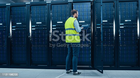 899720520 istock photo IT Engineer in High Visibility Vest is Working on Laptop in Data Center while Standing Before Server Rack. Running Diagnostics or Doing Maintenance Work. 1131198200