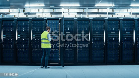 899720520istockphoto IT Engineer in High Visibility Vest is Working on Laptop in Data Center while Standing Before Server Rack. Running Diagnostics or Doing Maintenance Work. 1131198216