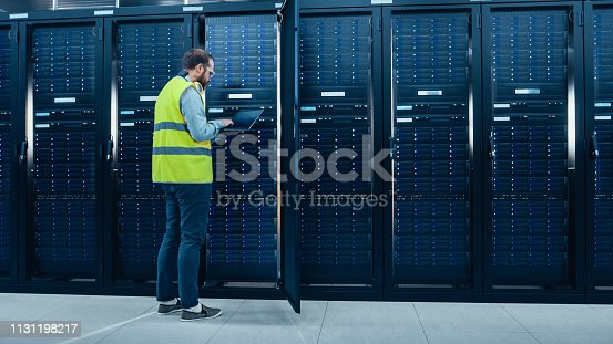 899720520istockphoto IT Engineer in High Visibility Vest is Working on Laptop in Data Center while Standing Before Server Rack. Running Diagnostics or Doing Maintenance Work. 1131198217
