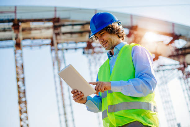 engineer in protective clothing on construction site with digital blueprints - civil engineer stock photos and pictures