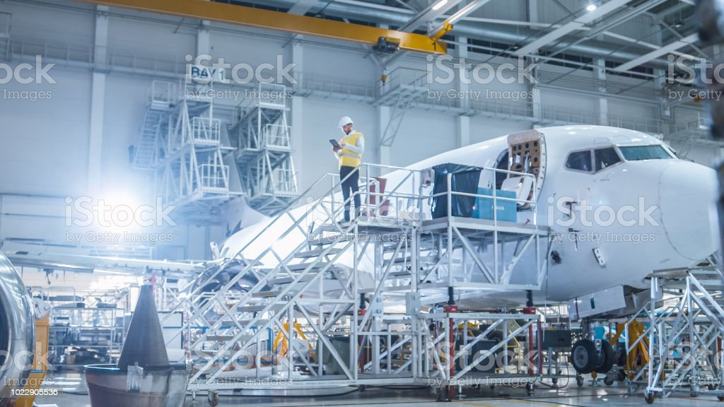 Engineer in Safety Vest Standing next to Airplane in Hangar stock photo