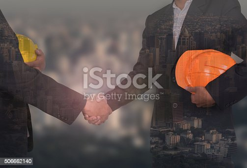 istock engineer in suite holding yellow helmet shaking hands 506662140