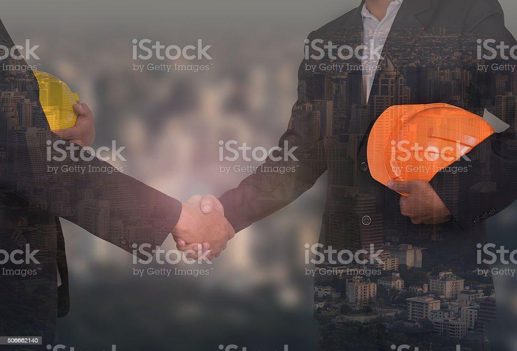 engineer in suite holding yellow helmet shaking hands stock photo