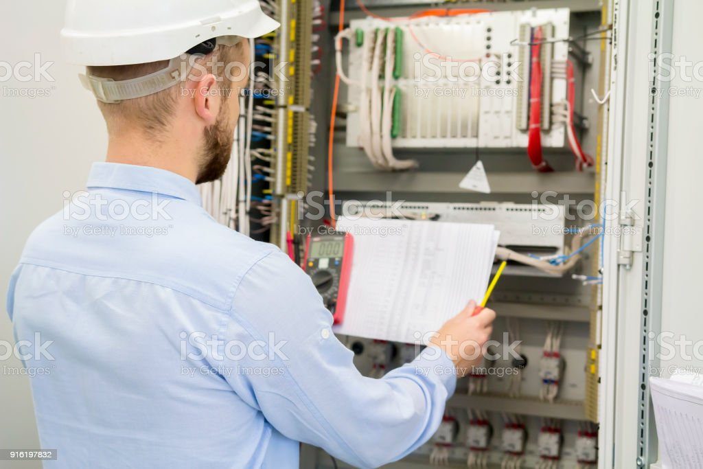 Engineer in white helmet reads design drawing against electric industrial panel. Service worker analyzes the electrical circuit in electrical automation control box with controllers. stock photo